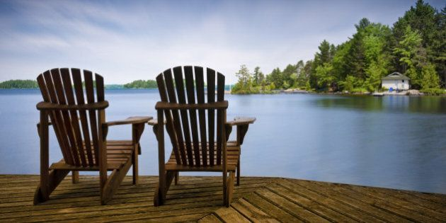 A couple of wooden Muskoka chairs sitting on the dock with a lake and cottages across in the background....