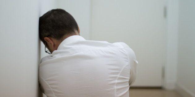 Man in white corridor in front of door, he looks tired/depressed/pensive.