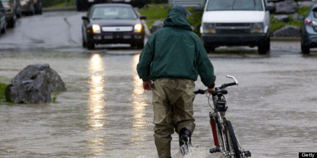 CANMORE, CANADA - JUNE 21: A man pushes his bicycle through the floodwater June 21, 2013 in Canmore,...