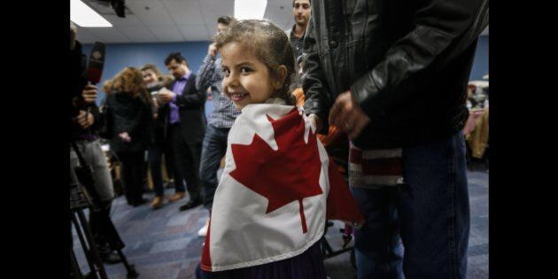 TORONTO, ON - DECEMBER 27: Reemas Al Abdullah, 5, wrapped herself in a Canadian flag prior to a dinner...