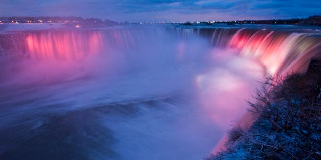 Niagra Falls is lit up at night as seen from