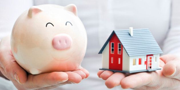 Hands holding piggy bank and house model. Housing industry mortgage plan and residential tax saving