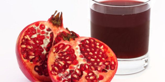 Glass of fresh pomegranate juice with ripe pomegranate cut into two halves, on a white