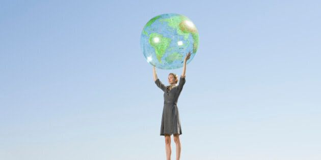 Businesswoman holding up globe