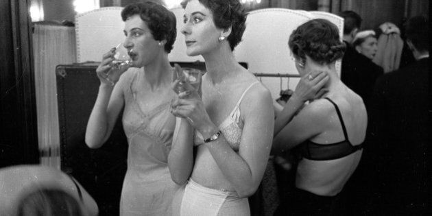Backstage, British models enjoy a glass of champagne as they wait to change into clothes designed by John Cavanagh. The designer is in Paris with four British models to show off his work and win orders from international buyers who don't come to London.