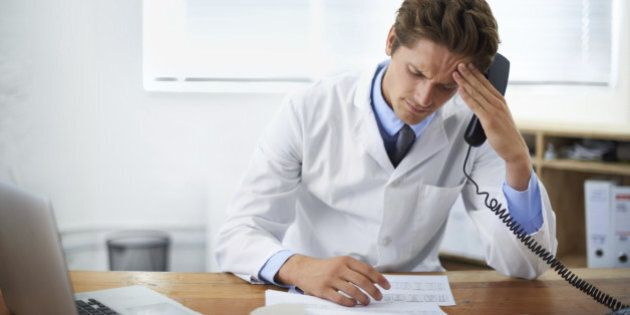 Shot of a concerned doctor sitting in his office and talking on the phone while looking over