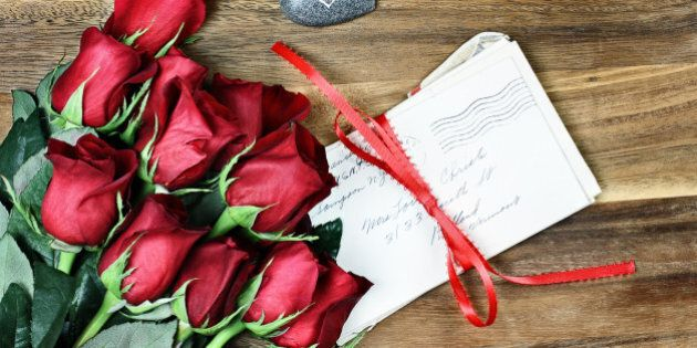 Long stem red roses with a stack of old letters tied with a red ribbon and card a little stone heart...
