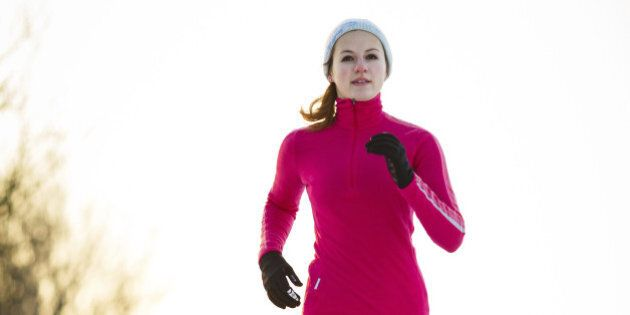 Winter running - Young woman running cross-country outdoors on a cold winter day (motion blurred image, color toned image)