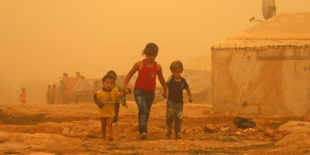 Syrian children walk amid the dust during a sandstorm on September 7, 2015 at a refugee camp on the outskirts...