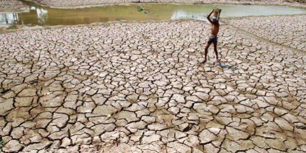 An Indian man carries a container of water on his head as he walks in a dry pond in a hot afternoon on...