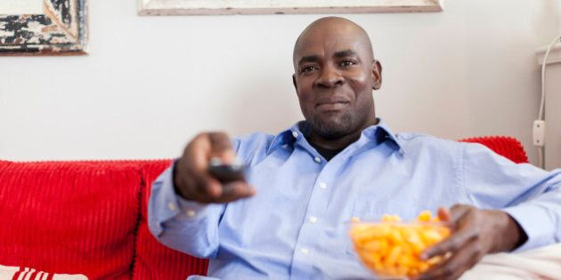 African male sitting on the sofa using a remote control to change the television channel , Cape Town,...