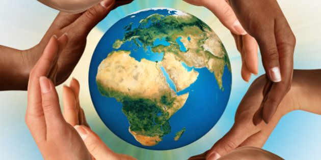 Conceptual symbol of multiracial human hands surrounding the Earth globe. Unity, world peace, humanity concept.
