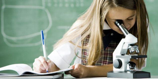 girl working in a classroom with a microscope