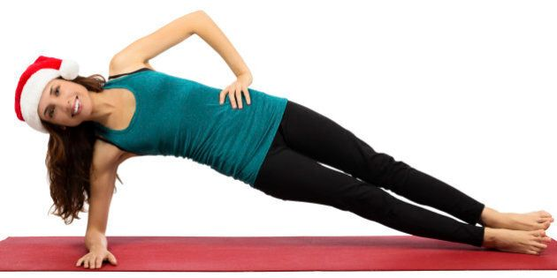 Attractive caucasian young christmas woman doing side plank pose in yoga