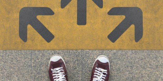 Pair of shoes standing on a road with three grey arrow on the yellow