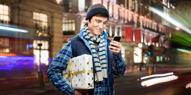 man holding shopping looks at mobilephone in