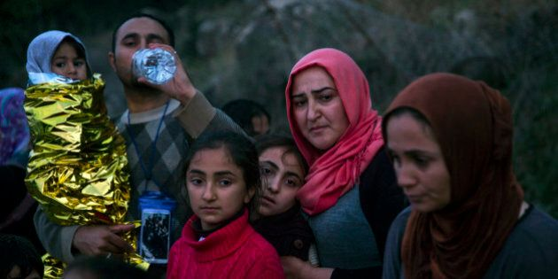 Syrian refugees drink water after arriving from Turkey at the Greek island of Lesbos on an overcrowded...