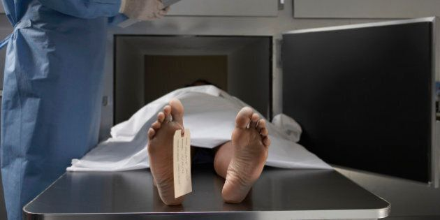 'Cadaver on autopsy table, label tied to toe,