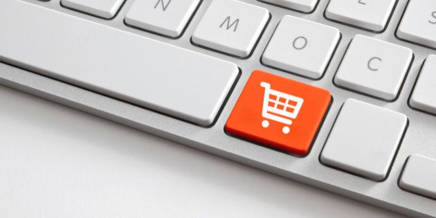 Online shopping concepts shooting of  white computer keyboard with orange shopping cart button.