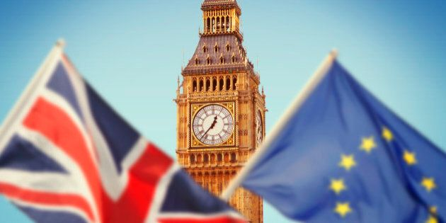 Big Ben in London and flags of Great Britain and European Union reflecting