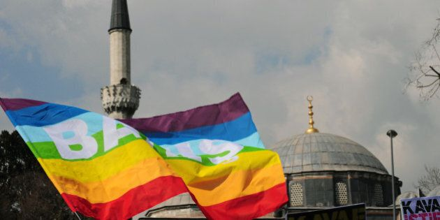 Turkish gay rights group (LAMBDA) activists wave peace flags infront of a mosque in Istanbul on March 16, 2010 during a demonstration against Family Affairs Minister Aliye Selma Kavaf. Some 60 activists denounced Kavaf and called for her resignation, as they accuse the Family Affairs Minister of insult, incitement to crime and incitement to enmity and hate -- crimes which are punishable by up to two, five and three years in jail respectively.  Kavaf, who is also women's minister in the Islamist-rooted government, said in a newspaper interview last weekend that she believed homosexuality was a 'biological disorder, a disease.' AFP PHOTO / MUSTAFA OZER (Photo credit should read MUSTAFA OZER/AFP/Getty Images)