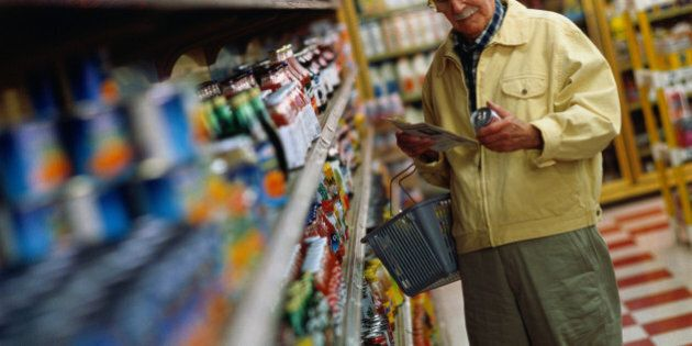 Mature man shopping for groceries, reading label of