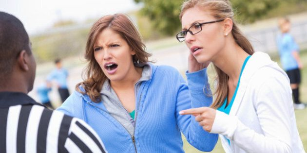 Angry soccer moms yelling at referee during kids' game.