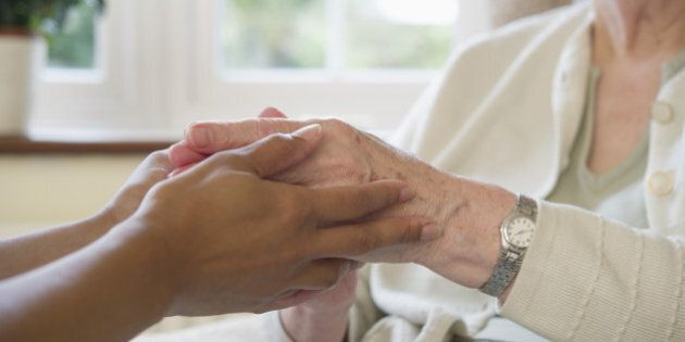 Close up of older woman and caretaker holding