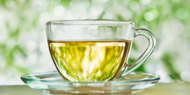 A glass cup and saucer with herbal tea against blurred foliage outdoors.
