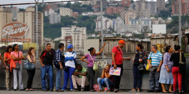 People line up expecting to buy food outside a supermarket in Caracas, Venezuela June 13, 2016. REUTERS/Ivan