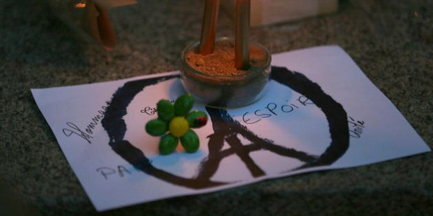 Candles are put on a peace sign combined with the Eiffel Tower at a temporary memorial for the victims...