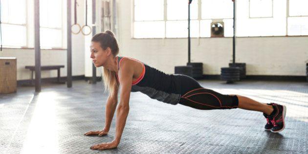 Woman making pushup's at urban gym at