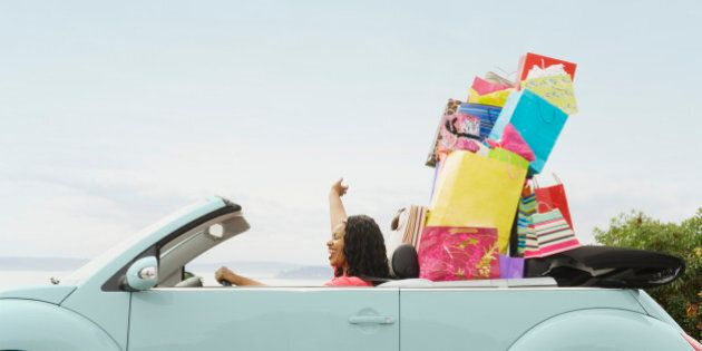 African woman in convertible with shopping