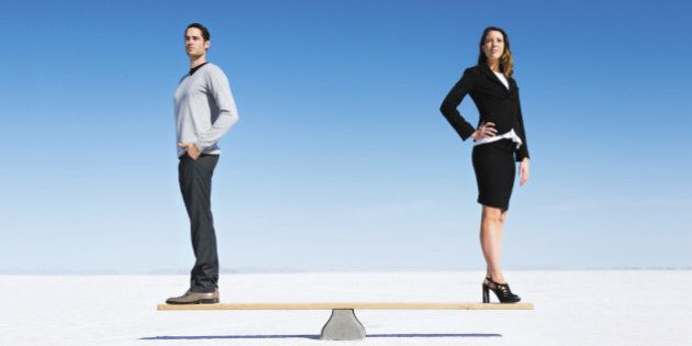 Businesswoman and businessman balanced on Seesaw. Gender equality concept.