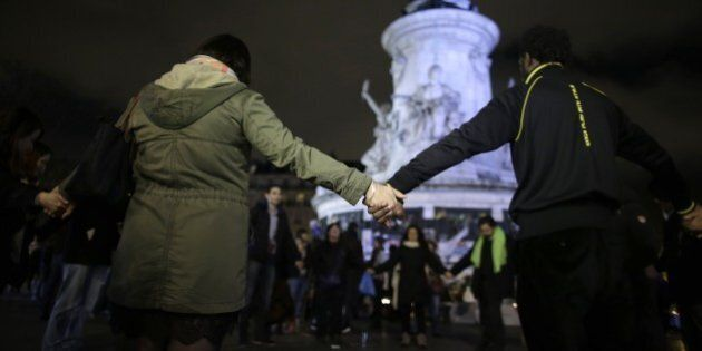 People hold hands near a makeshift memorial for the victims of a series of deadly attacks in Paris, at...