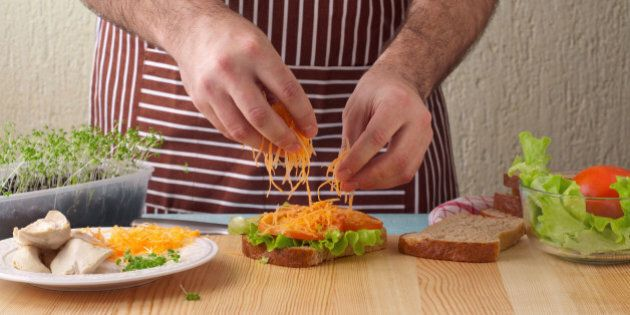 Man cooking big sandwich in home kitchen on a wooden table