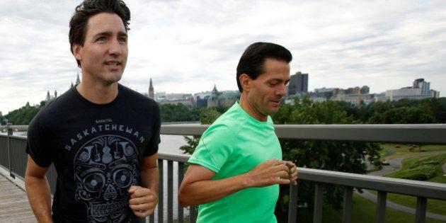 Canada's Prime Minister Justin Trudeau (L) runs with Mexico's President Enrique Pena Nieto across the...