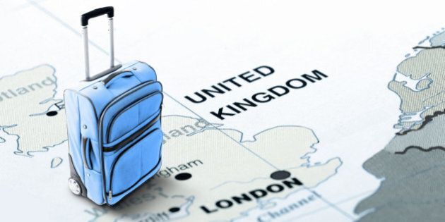 Travel the world and visit coutries. Orange suitcase on the map of United Kingdom. The image is toned in orange. Concept: Planning travel destinations or journey planning. Close-up view. Studio shot. Landscape orientation.