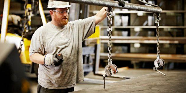 Steel worker preparing to move sheet of steel with crane