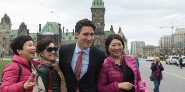 Canadian Liberal Party leader Justin Trudeau poses for a selfie with tourists as he walks from the parliament...