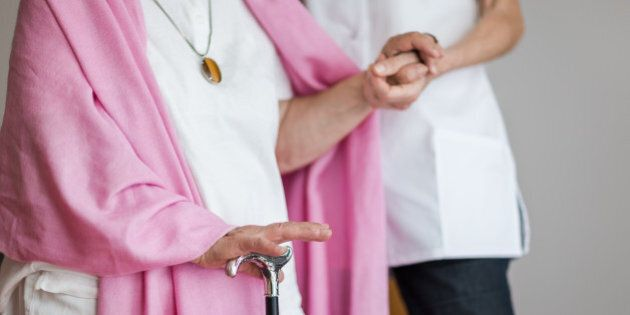 Senior woman with a crutch getting support from nurse. Lower section.