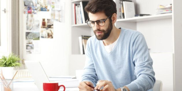 Young small business owner sitting at desk and working at