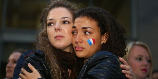 SYDNEY, AUSTRALIA - NOVEMBER 14:  Two woman embrace as Australians hold a vigil for victims of the Paris terror attacks at Martin Place on November 14, 2015 in Sydney, Australia. At least 120 people have been killed and over 200 injured, 80 of which seriously, following a series of terrorist attacks in the French capital.  (Photo by Daniel Munoz/Getty Images)