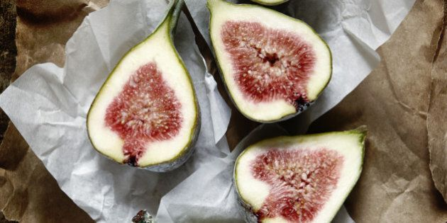 Cut figs on brown paper on a wooden kitchen surface