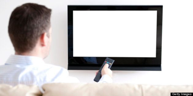 Man sits in sofa watching tv. He is pointing a remote at the tv. White screen: insert your own image
