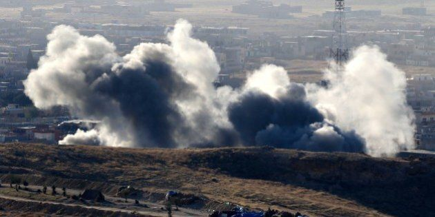 Smoke billows from the northern Iraqi town of Sinjar during an operation by Iraqi Kurdish forces backed...