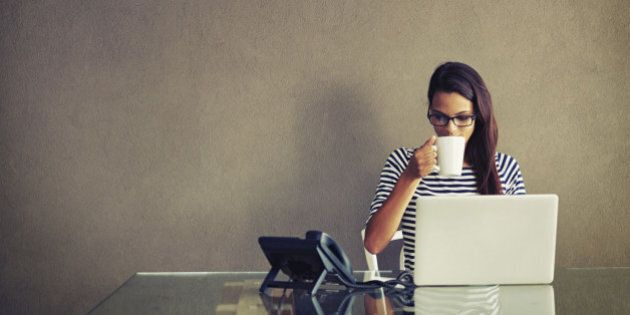 An attractive young businesswoman having coffee while working at her office