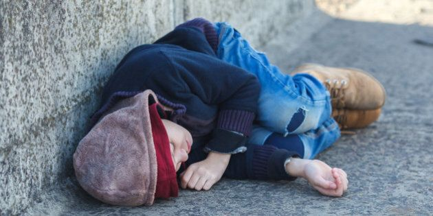young homeless boy sleeping on the bridge, poverty, city,