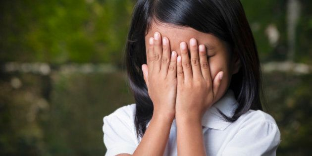 Shy 8 year old Filipino girl covering her face in Cebu City,