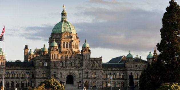 The historic Victoria, BC government building seen at sunset in the inner harbor of this beautiful